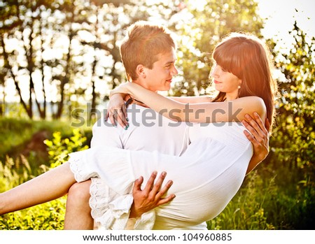 Happy couple in park, holding the girl in his arms - stock photo