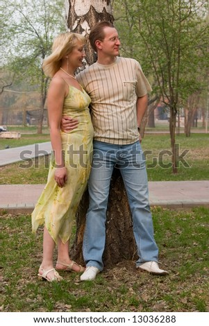 Happy couple in park. Man embraces woman.