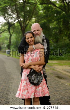 Happy couple in park older bearded Caucasian man with young Asian woman holding each other