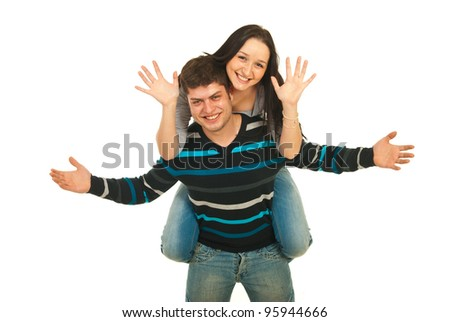 Happy couple in piggy back showing their palsm isolated on white background