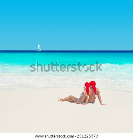 Happy couple in red santa hats at tropical sandy beach with yacht, christmas and new years vacation concept - stock photo