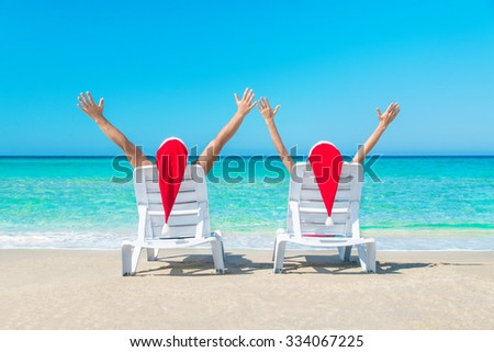 Happy couple in red Santa hats relaxing at romantic tropical beach on sun beds - Christmas or New Year's vacation in hot countries concept - stock photo