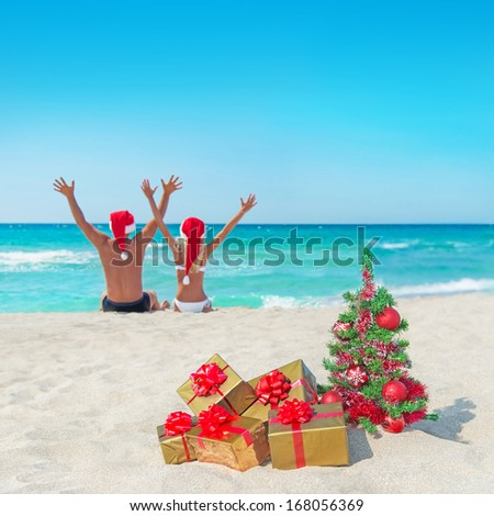 happy couple in santa hats hands up at sea beach with christmas tree and golden gift boxes - stock photo