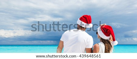 Happy couple in Santa hats looking to the seascape, holding their hands and celebrating Christmas on beach. New year vacation