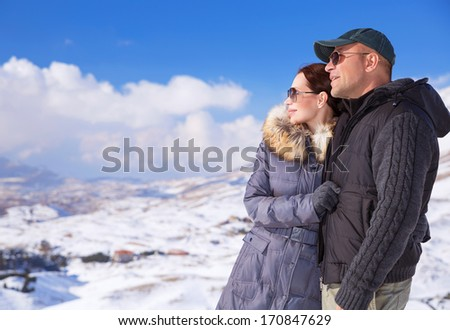 Happy couple in snowing mountains, active lifestyle, winter vacation, luxury wintertime resort, loving family, cold weather - stock photo