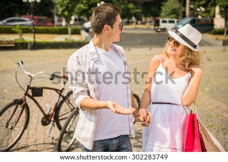Happy couple in sunglasses looking to each other on the city square. Woman holding shopping bags. - stock photo