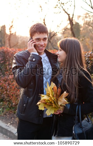 Happy couple in sunny autumn outdoors. Man talking on mobile phone - stock photo