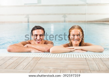 Happy couple in swimming pool enjoying hydromassage - stock photo