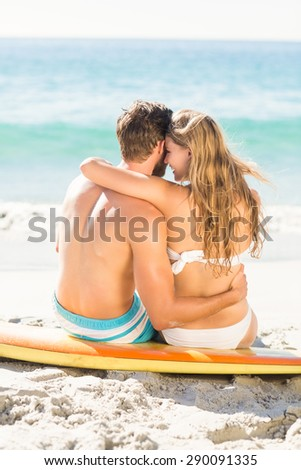 Happy couple in swimsuit embracing at the beach - stock photo