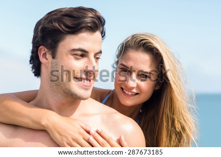 Happy couple in swimsuit looking at camera and embracing at the beach - stock photo