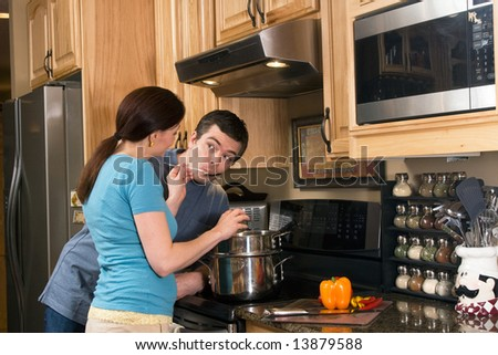 Happy couple in the kitchen near a counter, microwave, and a chopped pepper. She is letting him taste the food she is cooking on the stove.  Horizontally framed photograph - stock photo