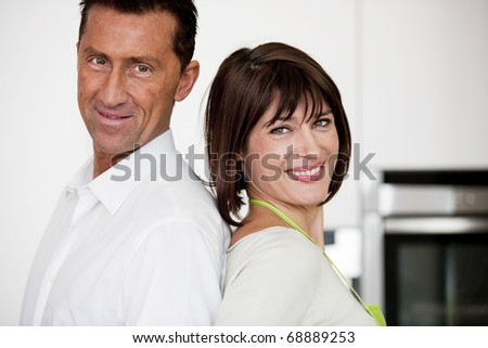 Happy Couple In The Kitchen, Smiling at camera - stock photo