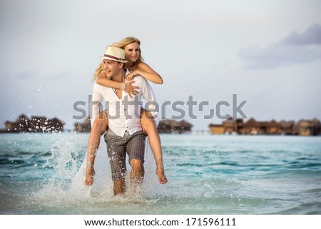 happy couple in the Maldives runs on water, the bride riding on the groom - stock photo