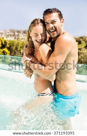 Happy couple in the pool embracing and laughing - stock photo