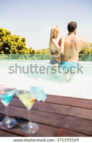 Happy couple in the pool with cocktails on the edge - stock photo