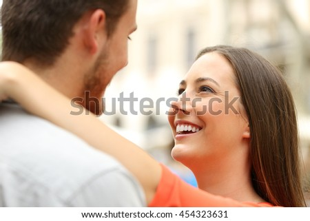 Happy couple in the street looking each other falling in love
