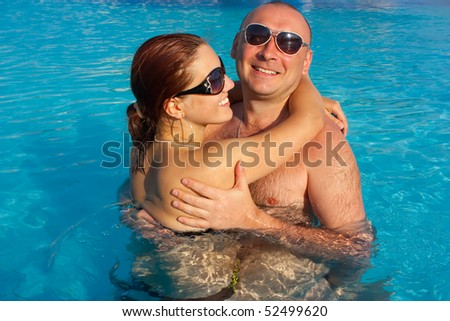 happy couple in the swimming pool in a hotel