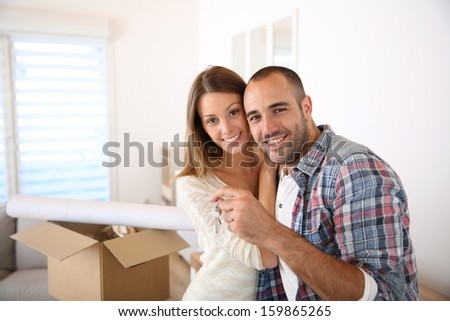 Happy couple in their new home holding key - stock photo