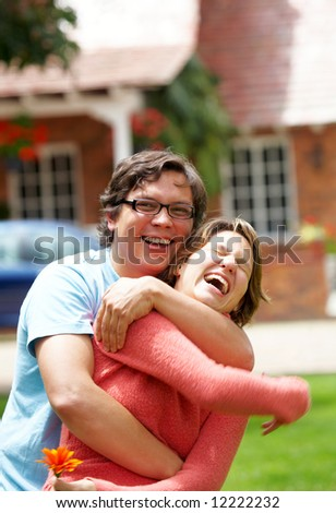 happy couple in their thirties smiling outdoors - stock photo