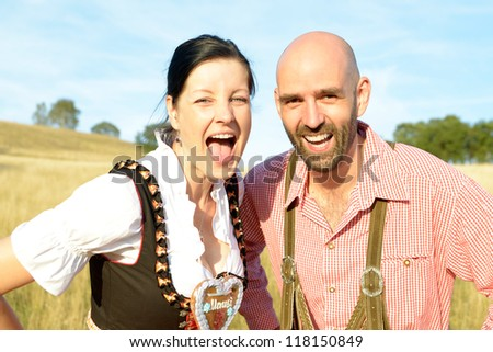 happy couple in traditional bavarian garbs - stock photo
