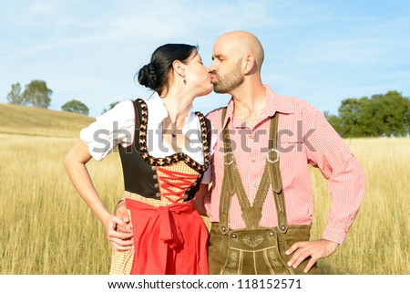 happy couple in traditional bavarian garbs kisses - stock photo