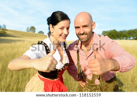 happy couple in traditional bavarian garbs with thumbs up - stock photo