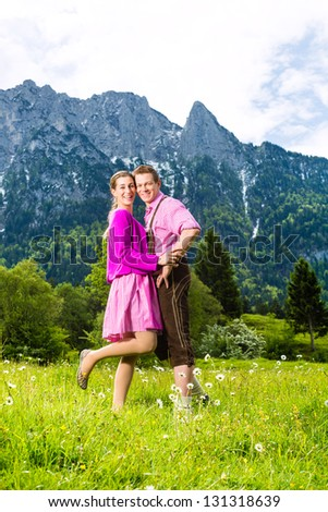 Happy Couple in traditional dress is standing in the meadow with mountain panorama