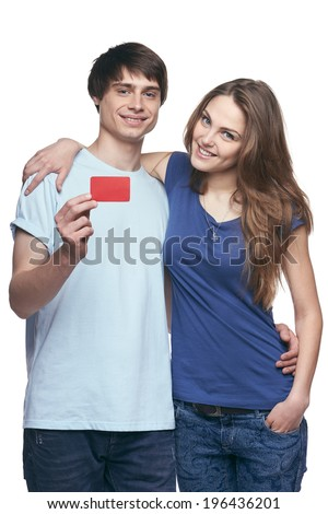 Happy couple in tshirts hugging, man showing blank credit card, on white background - stock photo