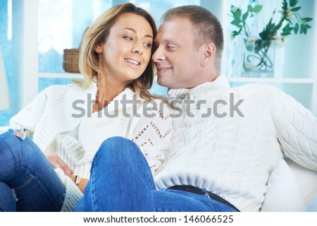 Happy couple in white pullovers and jeans talking to one another - stock photo