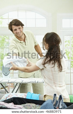 Happy couple ironing and packing clothes into suitcase, preparing for vacation. - stock photo