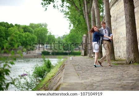 Happy couple is dancing on the Seine embankment in Paris - stock photo