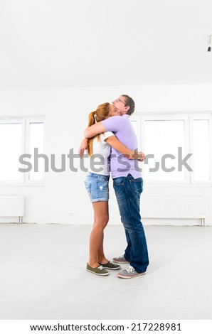 happy couple is embracing at their new empty apartment - stock photo