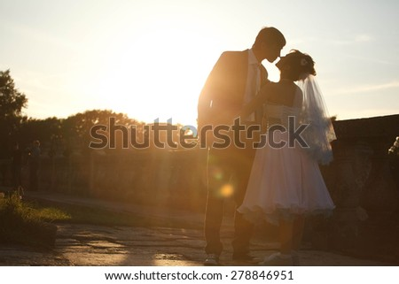 happy couple is hugging and kissing each other on background sunset