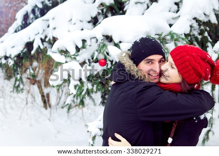 Happy couple is hugging in winter forest