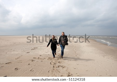 Happy couple is running on a beach
