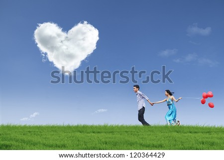 Happy couple is running together in green field while holding red balloons - stock photo