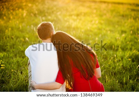 Happy couple is sitting in grass watching sunset - stock photo