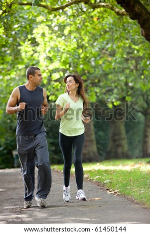 Happy couple jogging at the park - fitness concepts - stock photo