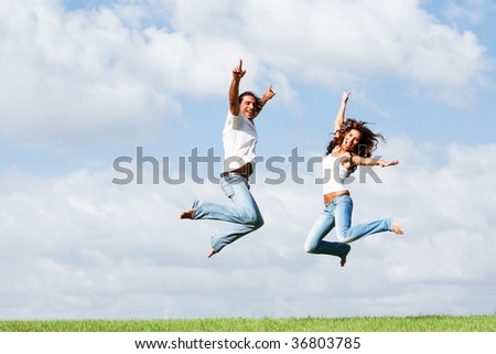 Happy couple jumping high of joy - stock photo