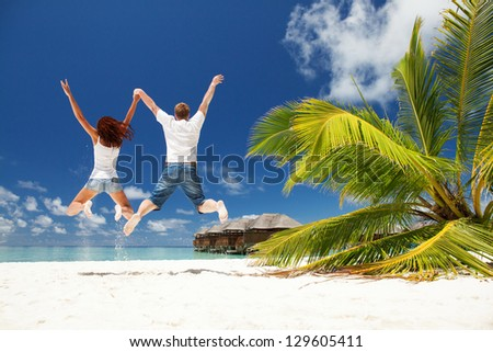 Happy couple jumping in the tropical beach - stock photo