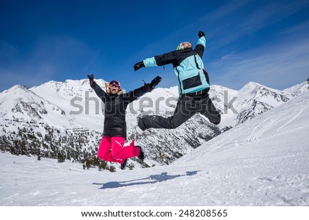 Happy couple jumping on the background of snowy mountains - stock photo