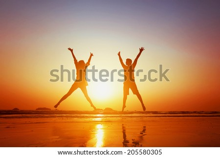 happy couple jumping on  the beach - stock photo