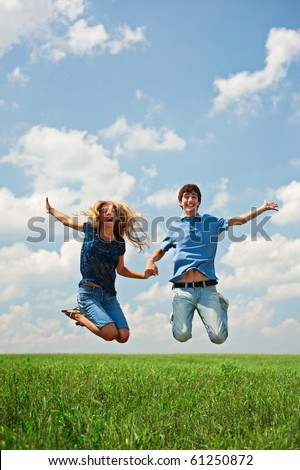 happy couple jumping on the green field - stock photo