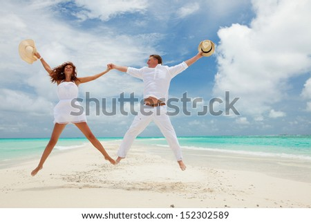 Happy couple jumping on the tropical beach - stock photo