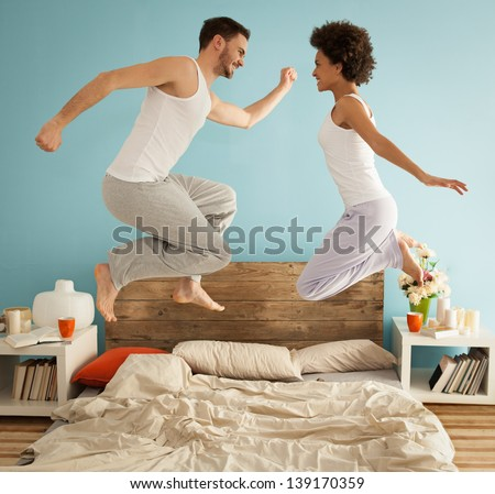 Happy couple jumping together on their bed. - stock photo