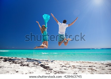 Happy couple jumping with outstretched arms on beach and enjoying their caribbean vacation. Back view - stock photo