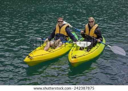 Happy Couple Kayaking on a lake together - stock photo
