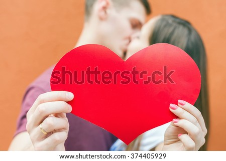 Happy couple kissing and holding a big heart symbol at red background. Image ready for International. Holiday concept of Valentine's Day, celebration