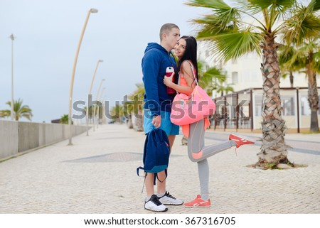 Happy couple kissing and smiling over palm trees on the beach background - stock photo