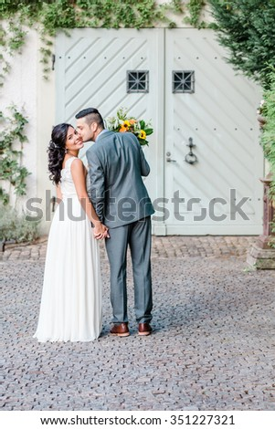 Happy couple kissing at the wedding day in front of the door. Full body portrait.  - stock photo